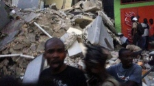This photo provided by Carel Pedre shows people running past rubble of a damaged building in Port-au-Prince, Haiti, Tuesday, Jan. 12, 2010. (AP / Carel Pedre)