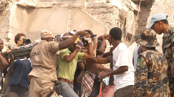People carry an injured person after an earthquake in Port-au-Prince, Haiti, Tuesday, Jan. 12, 2010. (AP / Radio Tele Ginen)
