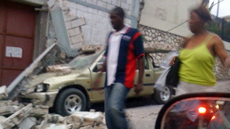 People walk past a crushed car and other rubble in Port-au-Prince on Tuesday, Jan. 12, 2010 after the largest earthquake ever recorded in Haiti. (AP / Carel Pedre)