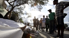 People look at earthquake victims lying on the street in Port-au-Prince, Haiti, on Wednesday, Jan. 13, 2010. (AP / Lynne Sladky)
