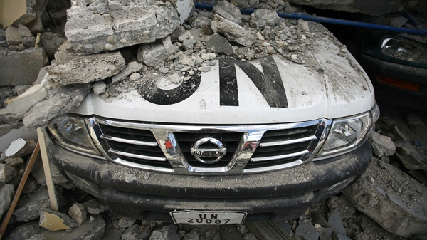 A UN car is covered in rubble the day after an earthquake hit Port-au-Prince, Haiti, Wednesday, Jan. 13, 2010. (AP / Ricardo Arduengo)