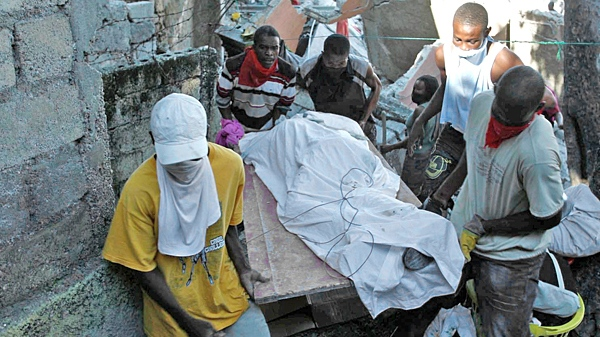 Men carry an earthquake victim after recovering him from underneath debris after the earthquake in Port-au-Prince, Haiti, Thursday, Jan. 14, 2010. (AP / Carl Juste, The Miami Herald)
