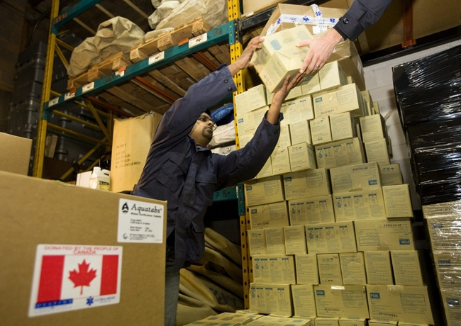 GlobalMedic volunteer Sean D'Souza, left, and Emergency Program manager Matt Capobianco carry boxes of supplies destined for Haiti from their Toronto headquarters Wednesday, Jan. 13, 2010. (Darren Calabre / THE CANADIAN PRESS)