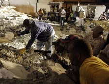Rescuers peer into rubble while trying to retrieve a trapped man from a collapsed building in Port-au-Prince, Haiti, Wednesday, Jan. 13, 2010. (AP / Julie Jacobson)