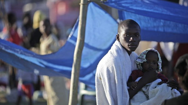 A man holds a child in a makeshift camp for earthquake survivors in the 31 Delmar neighbourhood in Port-au-Prince, Thursday, Jan. 14, 2010. Afraid to spend the night in their homes, most residents are camping out after a 7.0-magnitude earthquake struck Haiti Tuesday. (AP / Gregory Bull)