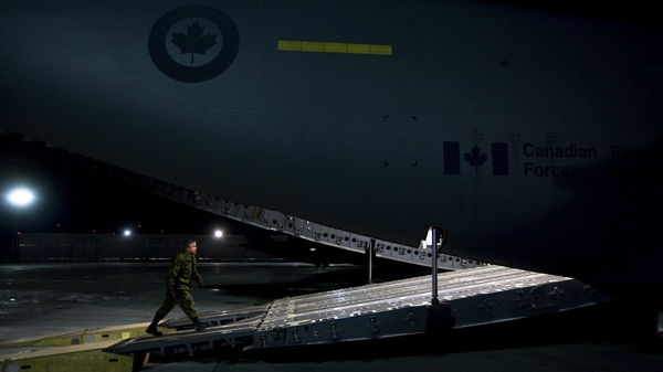 Military personnel prepare to load supplies on a CC-177 Globemaster on the tarmac at CFB Trenton for a Disaster Assistance Response Team (DART) humanitarian mission to earthquake ravaged Haiti, late Wednesday, Jan. 13, 2010. (Darren Calabrese / THE CANADIAN PRESS)