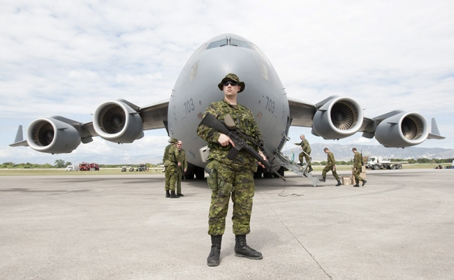 Cpl. Curtys Kennedy guards the Canadian Forces CC-177 Globemaster on its arrival in Port-au-Prince, Haiti Thursday, Jan. 14, 2010. (Adrian Wyld / THE CANADIAN PRESS)