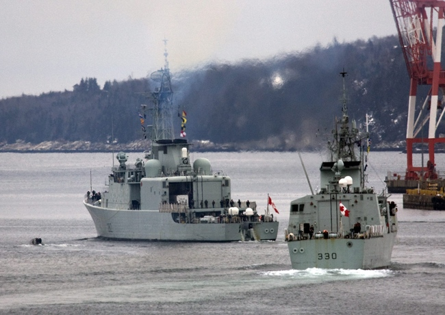 HMCS Halifax, right, and HMCS Athabaskan head out of the harbour in Halifax on Thursday, Jan. 14, 2010. The warships are heading to earthquake-ravaged Haiti to assist in the relief operation and expect to arrive early next week. (Andrew Vaughan / THE CANADIAN PRESS)