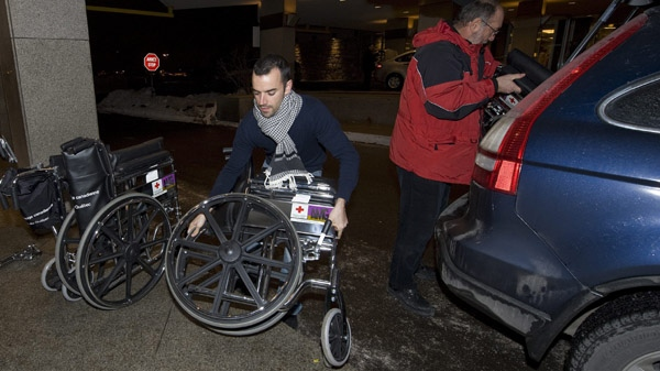 Red Cross employees unload wheelchairs at the Wyndham airport hotel in Montreal in preparation for tthe arrival of Canadians returning from Haiti on Thursday, January 14, 2010. (Peter McCabe/THE CANADIAN PRESS)