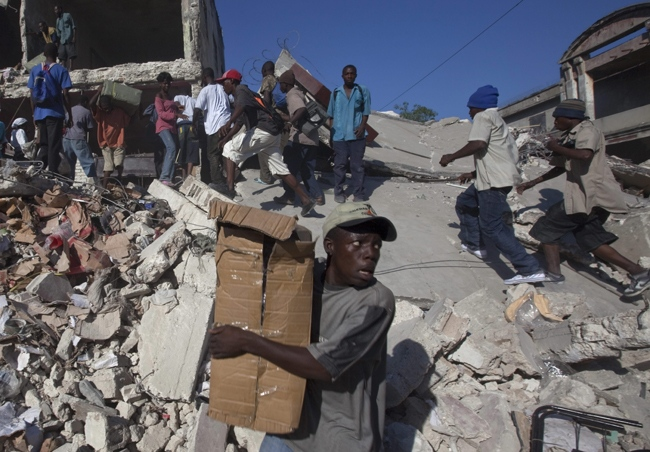 Scavengers look for goods amid the rubble of collapsed buildings in Port-au-Prince, Friday, Jan. 15, 2010. (AP / Ramon Espinosa)