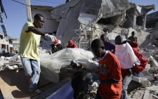 A victim is removed from a collapsed building following an earthquake in Port-au-Prince, Haiti, Friday, Jan. 15, 2010. (AP / Lynne Sladky)