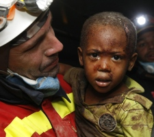 A Spanish rescuer carries two-year-old Redjeson Hausteen Claude after he was rescued from a collapsed home in the aftermath of the earthquake in Port-au-Prince, late Thursday, Jan. 14, 2010. (AP / Gerald Herbert)