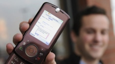 Stephen Simburg holds the mobile phone that he used when he found himself logged into a stranger's Facebook account recently, as he stands outside a coffee shop in Vancouver, Wash., Friday, Jan 15, 2010. (AP Photo/Greg Wahl-Stephens)