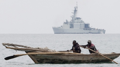 A fishing boat sails past HMCS Athabaskan off the coast of Leogane, Haiti, Tuesday Jan. 19, 2010. (Adrian Wyld / THE CANADIAN PRESS)