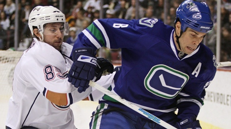 Edmonton Oilers' Sam Gagner, left, and Vancouver Canucks' Willie Mitchell battle for control of the puck during first period NHL action in Vancouver, B.C., on Saturday December 26, 2009. THE CANADIAN PRESS/Darryl Dyck