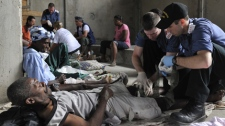 Master Cpl. J-P Somerset (left) and Able Seaman P J MacKenzie, from HMCS Athabaskan, give medical attention in Leogane, Haiti, Wednesday, Jan. 20, 2010. (Cpl. Johanie Maheu / Department of National Defence)