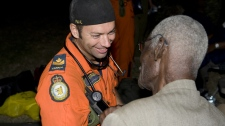 Master Cpl. Nicolat Meunier, member of the Search and Rescue team of 424 Squadron, Trenton, Ont., gives basic medical attention to an elderly man after he and his family arrived in the Canadian camp at Toussaint Louverture International Airport, Haiti on Wednesday, Jan. 20, 2010. (Cpl. Julie Belisle / Department of National Defence)