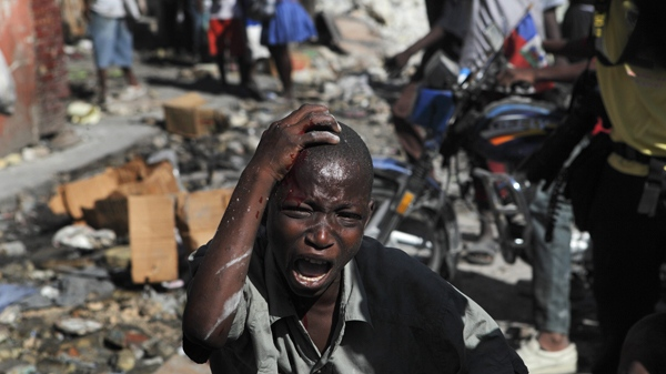 A boy bleeding from the head grimaces after he was beaten during looting of quake-damaged stores in Port-au-Prince, Thursday, Jan. 21, 2010. Sporadic looting broke up in the capital as earthquake survivors scavenged for anything they could find in the rubble left by the powerful earthquake that hit Haiti last week. (AP / Ramon Espinosa)