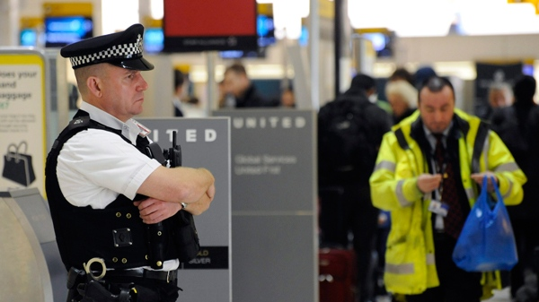 An Armed police officer maintains a presence at Heathrow Airport's Terminal 1 in London, on Monday Jan. 4, 2010. (AP Photo)