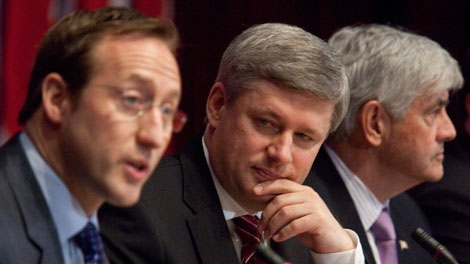 Minster of National Defence Peter MacKay, left, delivers an update on Canada's role in Haiti as Prime Minister Stephen Harper, centre, listens and Minister of Foreign Affairs Lawrence Cannon looks on at the Department of Foreign Affairs in Ottawa on Saturday, Jan. 23, 2010. (Pawel Dwulit / THE CANADIAN PRESS)