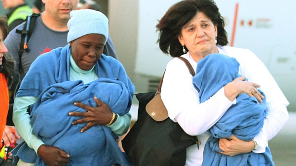 Women carry two of 24 orphaned Haitian children arriving from earthquake stricken Haiti, at the Ottawa airport Sunday January 24, 2010. Fred Chartrand / THE CANADIAN PRESS)