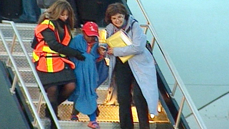 A Haitian orphan is helped off a plane and into Ottawa's airport, early Sunday morning, Jan. 24, 2010.