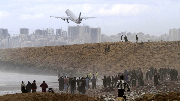 An airplane takes off as Lebanese soldiers gather debris on the shore after an Ethiopian Airlines plane crashed in the sea, in Khalde, south of Beirut, Lebanon, Monday, Jan. 25, 2010. (AP / Mohammed Zaatari)