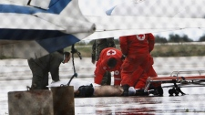 Lebanese Red Cross workers move a body retrieved from the sea after an Ethiopian Airlines plane crashed in the Mediterranean, at the military airbase in Beirut airport, Lebanon, Monday, Jan. 25, 2010. (AP / Hussein Malla)