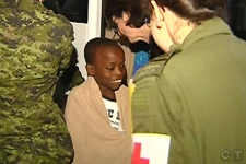 A young boy is all smiles as he gets ready to board a flight to Canada (Jan. 24, 2010)