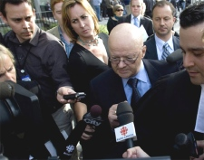Dr. Roger Perrault is questioned by the media as he leaves the courthouse after being acquitted in the tainted blood case on Oct. 1, 2007 in Toronto. (CP / Adrian Wyld)