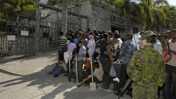 Canadian Forces members provide security as a crowd of people gather in front of the Canadian Embassy in hopes of being evacuated to Canada in Port au Prince, Haiti, on Monday, Jan. 25, 2010. (M.Cpl. David Hardwick / Department of National Defence)