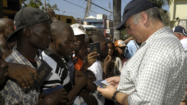Migration Integrity Officer, Brian Crocker (right), examines the passport of a man in front of the Canadian Embassy in Port au Prince, Haiti, Monday, Jan. 25, 2010. (Master Cpl. David Hardwick / Department of National Defence)