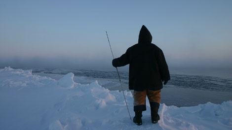 An Inuit hunter is seen looking out from the ice-edge of Igloolik in November 2005. The photographer, Dr. James Ford, returned to the same spot a year later and found it to be open water -- an example of ice that freezing later and later each year. (Courtesy of James Ford)
