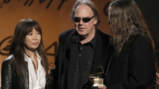 "Jenice Heo, left, Neil Young, center, and Gary Burden accept the award for best boxed or limited edition for ""Neil Young Archives Vol. 1"" at the Grammy Awards on Sunday, Jan. 31, 2010, in Los Angeles. (AP Photo/Matt Sayles)"