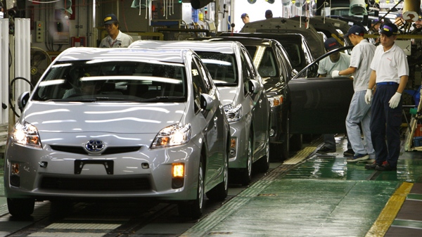 Workers give the final checkup on new Prius hybrid vehicles at Toyota Tsutsumi Plant in Toyota, central Japan, June 5, 2009. (AP / Shizuo Kambayashi)