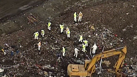 Police in hazard suits dug through garbage at the Delta landfill, south of Vancouver, as part of a criminal investigation on Feb. 5, 2010.