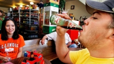 Leslie Little, left, and Ryan Singleton, right, of Champaign, Ill., enjoy a soda pop in Homer, Ill. (AP / Seth Perlman)