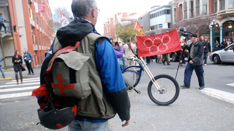 Chris Shaw, working as a street medic, surveys a crowd of anti-Olympic activists in Victoria on the first day of the torch relay.