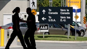Canadian border guards are silhouetted as they replace each other at an inspection booth at the Douglas border crossing on the Canada-USA border in Surrey, B.C., on Thursday August 20, 2009. (Darryl Dyck / THE CANADIAN PRESS)
