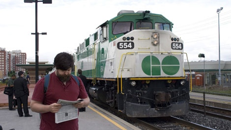 A commuter reads a newspaper as a GO train arrives at the Oakville, Ont. GO Station, Tuesday, June 30, 2009. (Richard Buchan/THE CANADIAN PRESS)