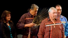 Justice Murray Sinclair, Chair of the Residential Schools Truth and Reconciliation Commission (TRC), is smoked in as Commissioner Marie Wilson, left, and Commissioner Chief Wilton Littlechild, right, look on as they take part in a ceremony in Gatineau, Quebec on July 16, 2009. (Sean Kilpatrick / THE CANADIAN PRESS)