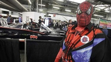 A man dressed in a Spider-Man costume walks by a car from the Batman television show at the Big Apple Comic Con in New York, Friday, Oct. 16, 2009. (AP Photo/Richard Drew)