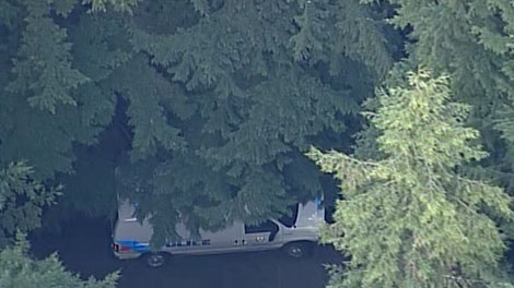 A Vancouver police car is seen parked in the area where a body was discovered in Vancouver's Stanley Park on Thursday, Feb. 25, 2010.  The deceased is believed to be that of former sitcom star Andrew Koenig.