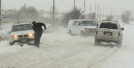 A man digs his vehicle out of a snowbank on Langstaff Road west of Highway 27 in Vaughan on Feb. 26, 2010. (Tom Stefanac/CTV.ca)