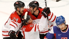Canada's Corey Perry, Ryan Getzlaf and Brenden Morrow celebrate Getzlaf's second period goal as Slovakia's Marian Hossa skates away during the second period of the men's hockey semi-final on Friday, Feb. 26, 2010. (AP Photo/The Canadian Press, Ryan Remiorz)