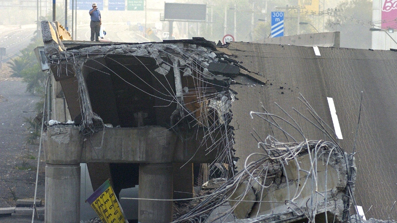 A man looks at a collapsed road in Santiago Saturday Feb. 27, 2010. (AP / Carlos Espinoza)