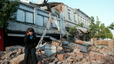 A resident sits on the debris of a collapsed house in the city of Talca, some 275 kilometres south of Santiago, Chile, Saturday, Feb. 27, 2010. (AP / Sebastian Martinez)