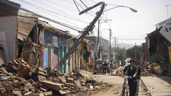 A resident walks along a damaged street in Talca, Chile, Saturday, Feb. 27, 2010, after a powerful earthquake struck central Chile. (AP / Roberto Candia)