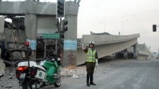 A police officer controls the traffic aside of an elevated highway that collapsed in Santiago following a powerful earthquake in central Chile, Saturday, Feb. 27, 2010. (AP / David Lillo)