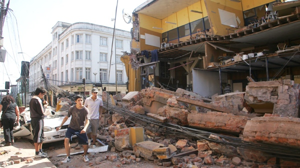 People walk near a destroyed building in Concepcion, southern Chile, Saturday, Feb. 27, 2010. (AP Photo)